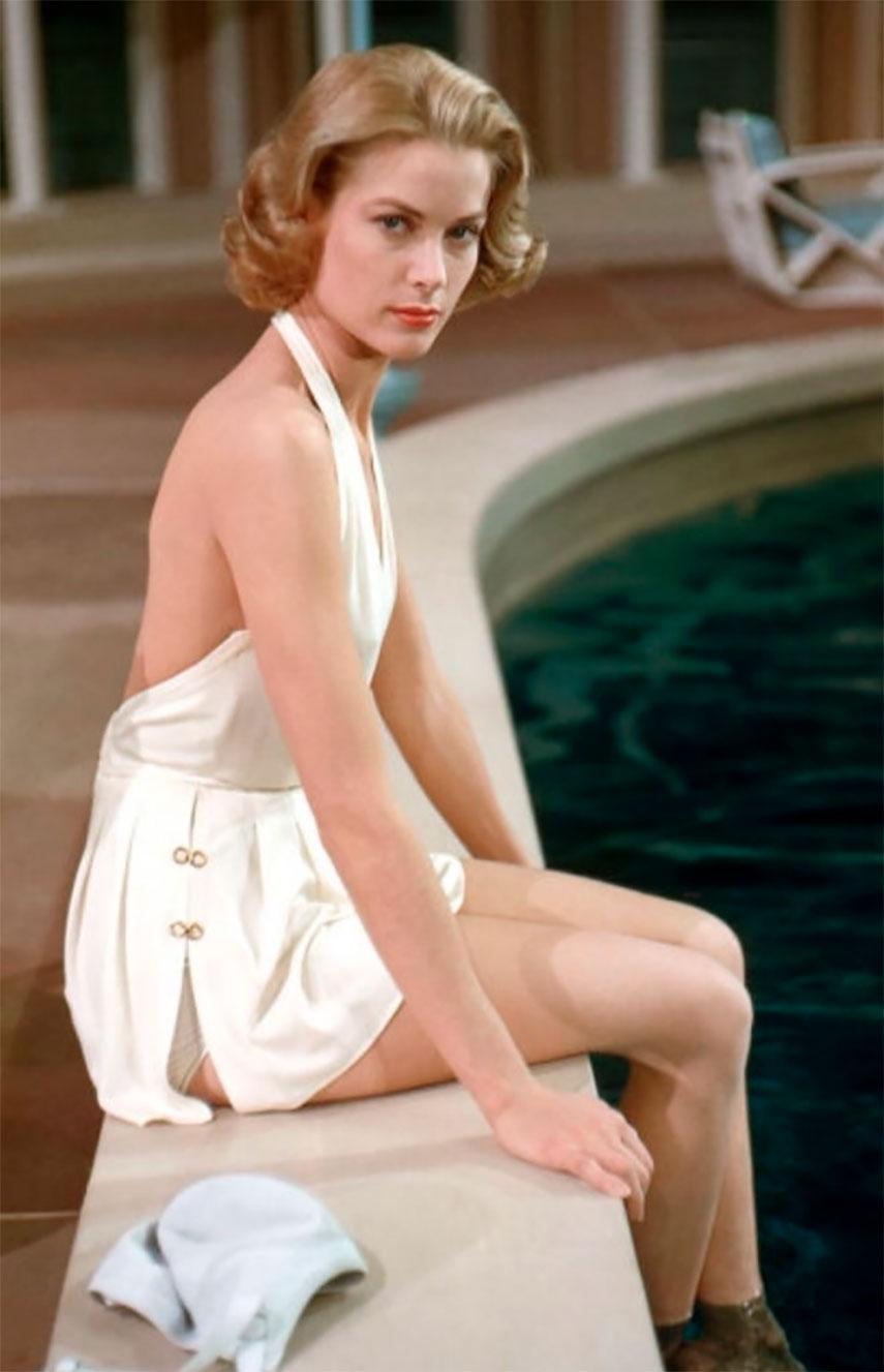 Grace Kelly in posa sulla piscina con costume bianco intero