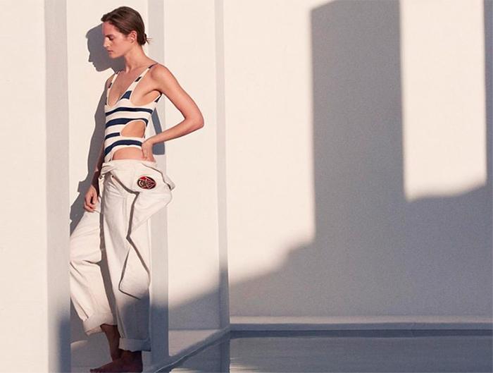 modella appoggiata al muro indossa costume intero righe bianco blu di ralphlauren