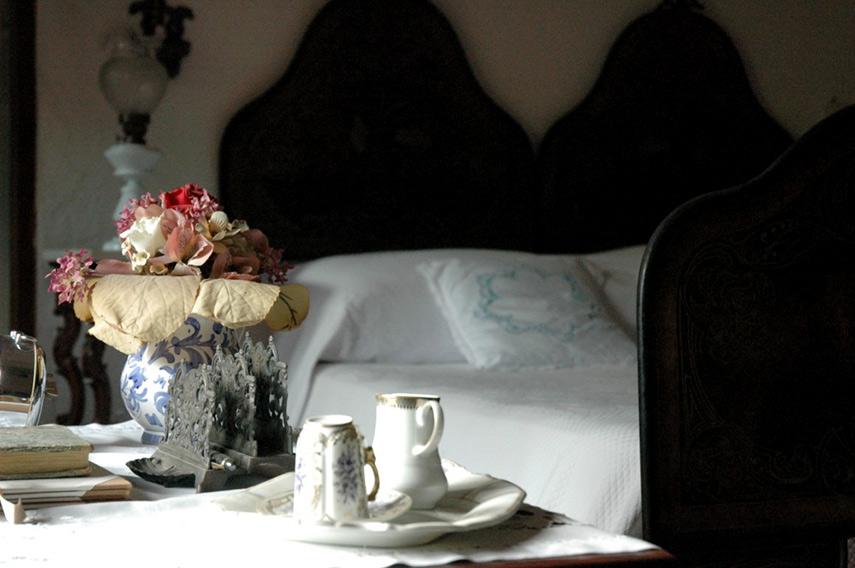 La Masseria Moscala - particolare sulla colazione in porcellane con sfondo camera rustica (letto) con biancheria di prezioso e candido cotone bianco