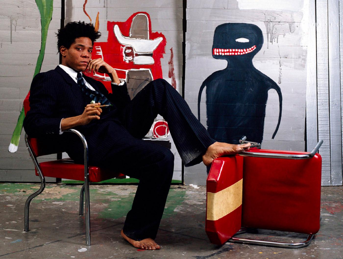 Jean-Michel Basquiat - l'artista a piedi scalzi con abito e cravatta scuri in posa da seduto