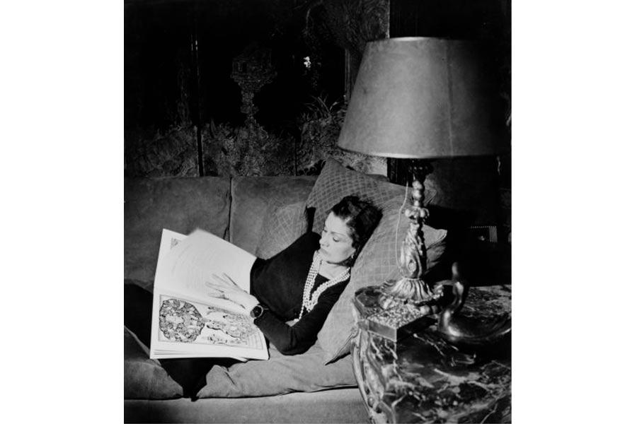 gabrielle chanel in una posa rilassata sul divano, mentre legge. Foto bn anni 60