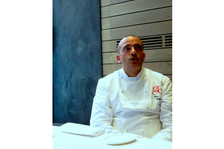 pino cuttaia - lo chef parla seduto ad un tavolo con la divisa