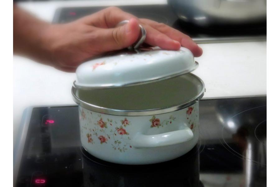 pino cuttaia - lo chef in cucina, scoperchia un pentolino piccolo in ceramica bianca con fiorellini