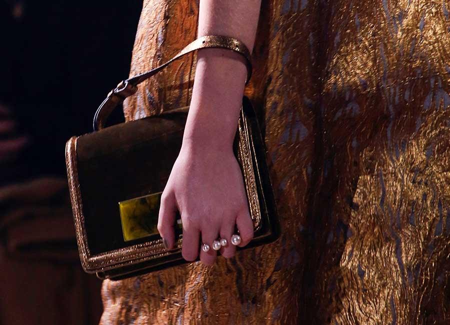Alta Moda: Borsa in velluto dorato con chiusura clic clac e decorata con piume cangianti. Credits: Dries Van Noten