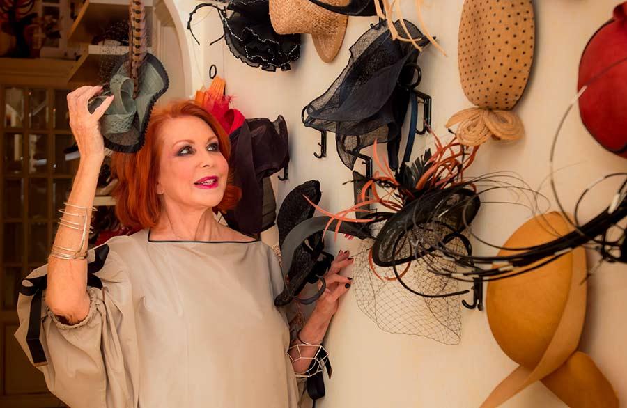 Marina Ripa di Meana mostra la sua elegante collezione di cappellini appesi al muro