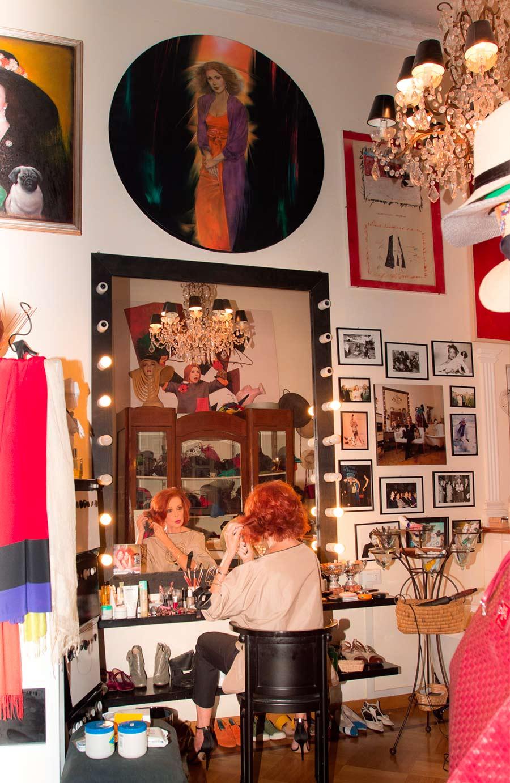Marina Ripa di Meana seduta davanti all'antico specchio old style circondata da foto e quadri alle pareti, dettaglio di un elegante lampadario barocco