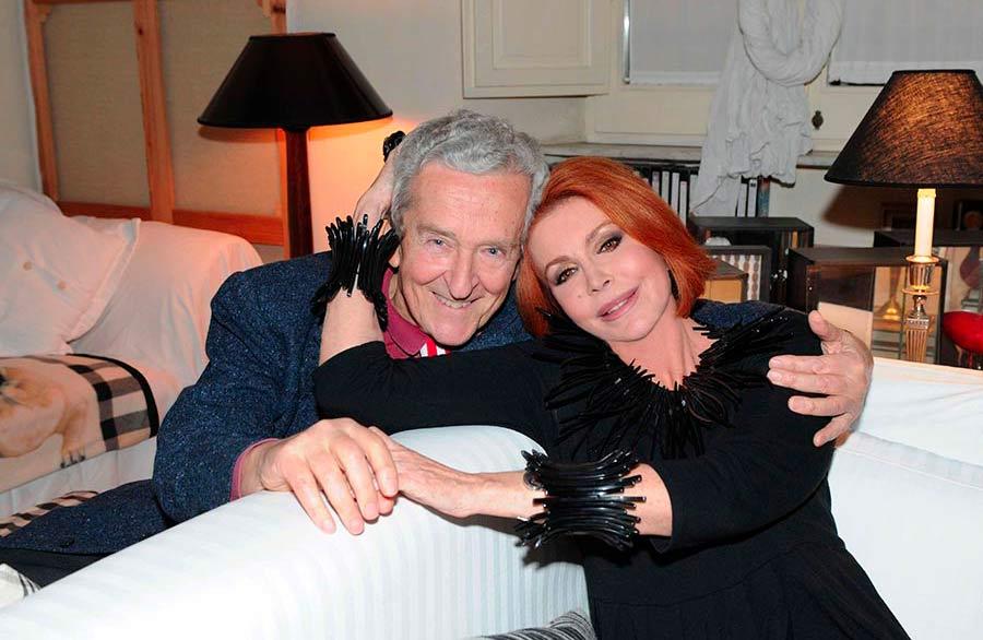 Marina Ripa di Meana con suo marito Carlo, abbracciati un un angolo del divano bianco di alto design italiano