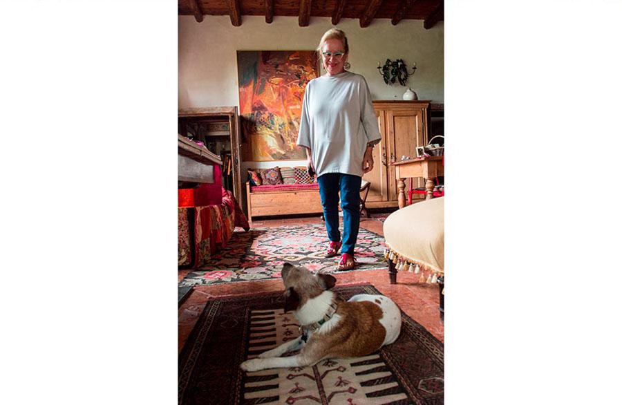 Olimpia Biasi, pittrice - interno casa , in piedi sorride al suo cane che la guarda