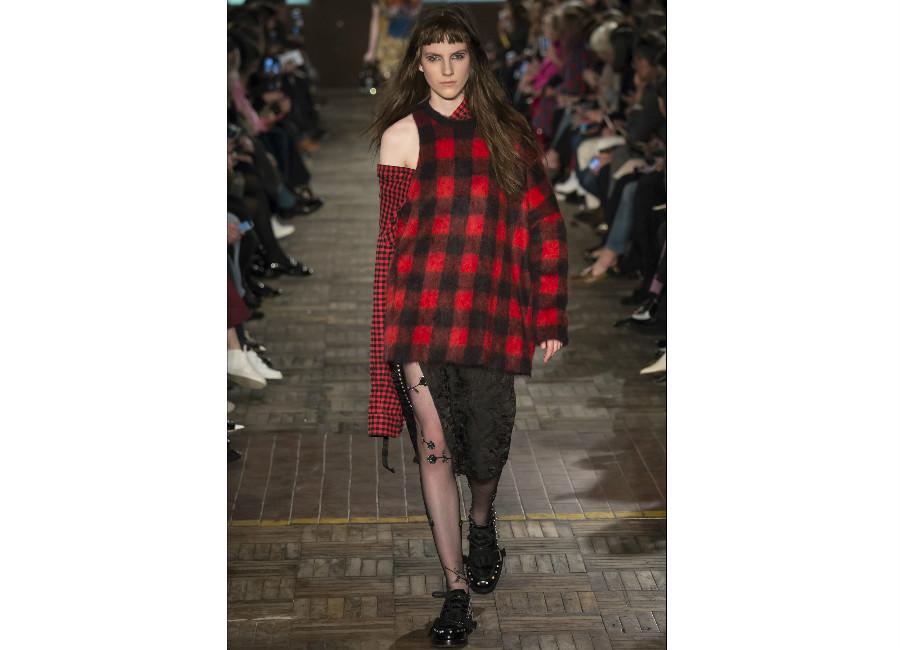 tartan-maglia-monospalla-a-quadri-rossa-e-nera-portata-con-una-gonna-in-pizzo-e-calze-velate-nere-credits-camera-della-moda
