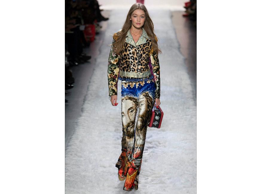new york fashion week-Jeremy Scott F/W 2017-2018_Gigi Hadid indossa giubbotto leopardato con maniche fiorate e pantalone velluto con immagini sacre in chiave pop
