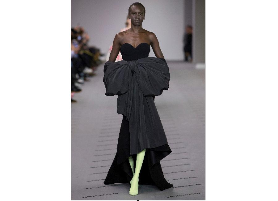 Paris Fashion Week-F-W 2017-2018_Balenciaga-abito nero con scollo a cuore e grande fiocco anteriore portato con stivali lunghi verde acido