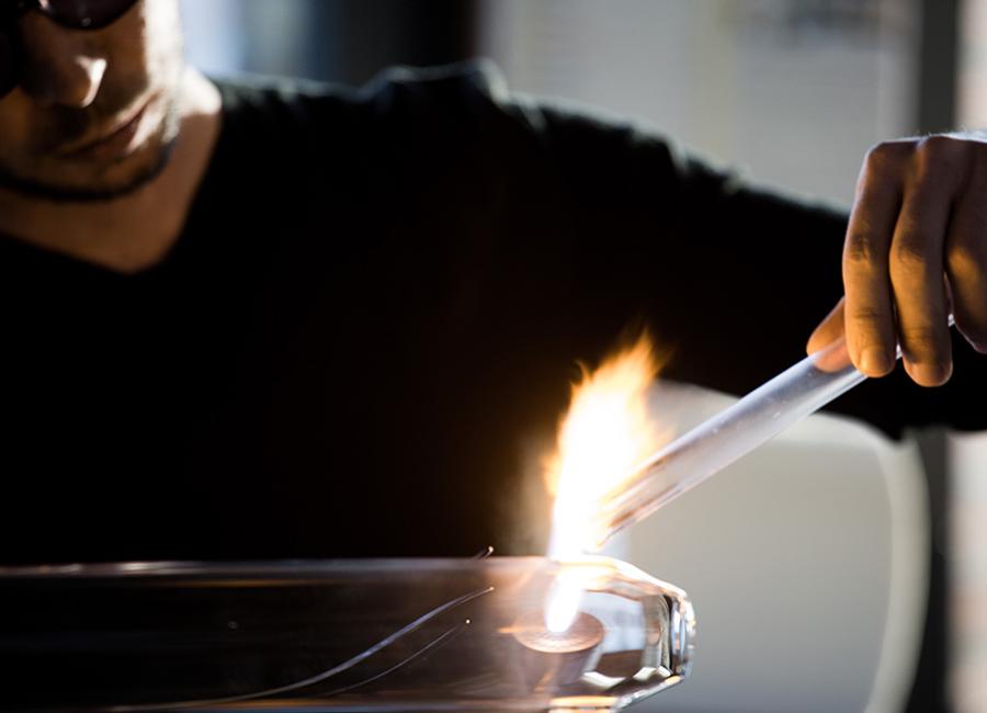 Il Maestro Simone Crestani al lavoro nel suo atelier, mentre crea con la lavorazione a lume le sue fantastiche forme naturalistiche nel vetro borosilicato trasparente. © Laila Pozzo