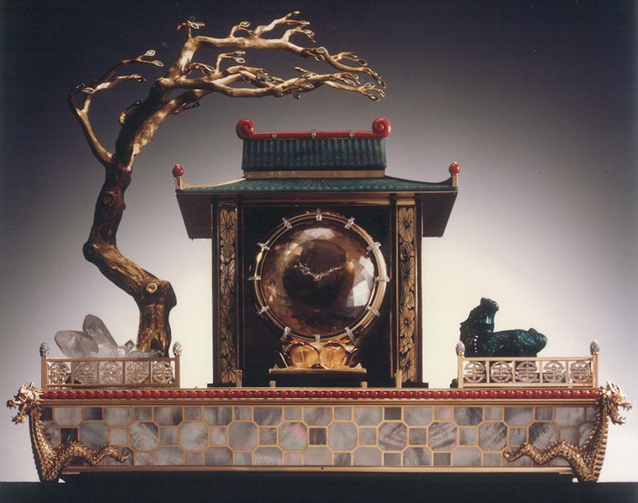 """pendole Cartier - Pendola misteriosa Tempio cinese del drago – fine anni '80 - L'estetica ricorda irrimediabilmente il famoso """"Necessaire de bureau japonais"""" del 1926. - Seimila ore di lavoro per un'opera d'arte eccezionale, messa in azione con una lieve pressione sul drago che addirittura accende l'illuminazione interna del tempio e fa aprire la porta centrale. In una seconda fase la pendola, il vero tesoro del tempio, avanza fino a collocarsi al suo esterno. Il centro del quadrante è realizzato con un citrino rotondo sfaccettato di 2.700 carati mentre il drago, scolpito nel XIX secolo, è in malachite."""