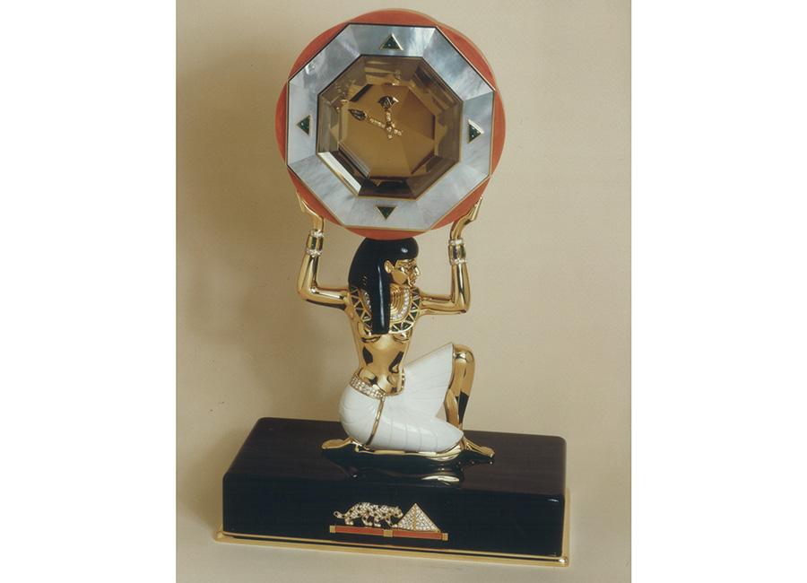 """pendole Cartier: Cartier - Archivio- Pendola misteriosa """"Dea Egizia"""" - 1988 - Da un punto di vista stilistico questa versione di pendola misteriosa deriva dalle """"Pendules à sujet"""" dell'epoca di Luigi XV e XVI in cui il movimento dell'orologio era appoggiato al dorso di un animale. Qui a sostenere il quadrante troviamo una divinità egizia, un soggetto ispirato alla collezione di gioielleria presentata nel 1988 ed un tema molto usato fin dai primi anni del '900, principalmente nel periodo Art Déco. La Dea sostiene un quarzo citrino facettato, contornato di madreperla e corallo. Le lancette sono di oro giallo, tempestate di brillanti, smeraldi e rubini calibrati. Il perizoma è modellato in """"cacholong"""" una particolare varietà di opale bianco porcellana, la capigliatura della dea è in onice. La pettorina tempestata di brillanti e smeraldi è accompagnata con bracciali di diamanti."""