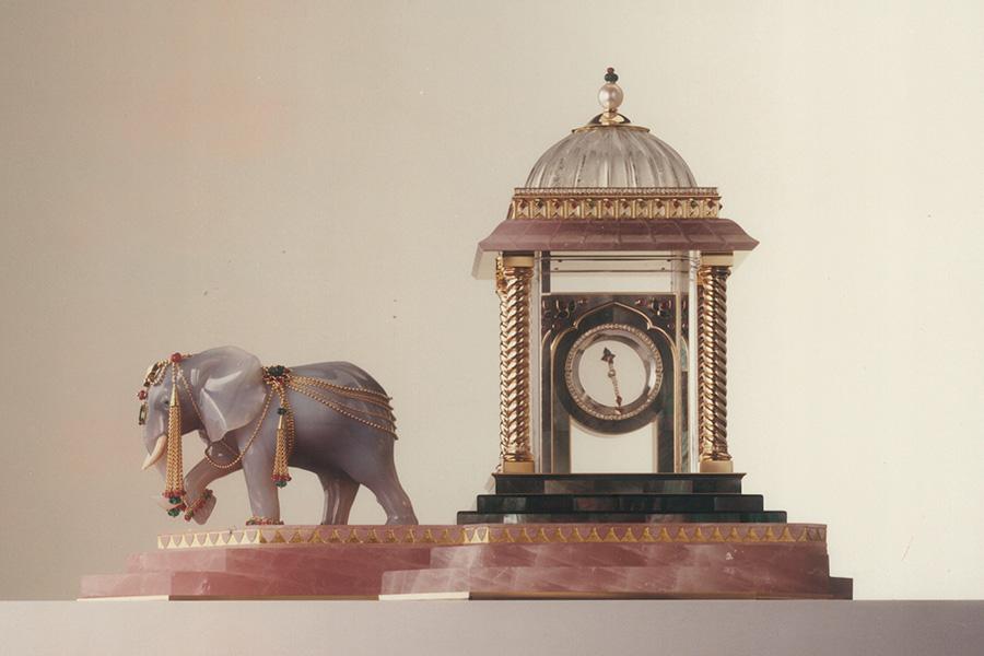 """pendole Cartier – Archivio - Pendola misteriosa - JAI, l'elefante – 1990 Nel 1990 Cartier continua il suo lungo sodalizio con l'India ed i suoi fasti presentando la collezione """"La Route des Indes"""". Una curiosità riguardo all'elefante Jai, scolpito a tutto tondo in agata grigia: l'animale corrisponde alla specie africana e non a quella indiana ma seppur di un altro continente colpisce per la raffinatezza del savoir faire! L'orologio è stato eseguito attraverso 1900 ore di lavoro. Il tempietto che ospita il quadrante misterioso di cristallo di rocca è costruito in quarzo rosa, come la base a tre gradini. Abbellito con un intarsio di madreperla è sormontato di una perla birmana, smeraldo e rubino. Brillanti (8,62 cts), rubini (19 cts) e più di 30 carati di smeraldi arricchiscono l'oggetto, sostenuti da quasi un chilo d'oro."""
