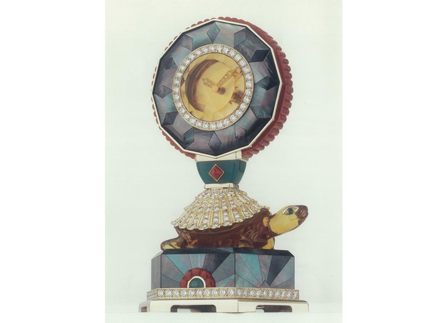 """pendole Cartier – Pendola misteriosa – anni 1990 - Derivazione delle """"Pendules à sujet"""" in cui il movimento è appoggiato sul dorso di un animale, in questo caso la tartaruga, simbolo della longevità nella cultura cinese. Fu Jean Toussaint, celebre collaboratrice di Louis Cartier, già nell'alta gioielleria della Maison dal 1933 e poi anche nell'orologiera, ad ispirare nel 1962 la prima pendola misteriosa con l'evocazione della tartaruga, insieme alla pantera, uno dei suoi animali prediletti. Scolpita nell'ambra, la tartaruga supporta un citrino facettato. Oro giallo, brillanti (10 cts), madreperla, corallo, agata verde. Movimento meccanico (8 giorni di riserva di carica), 500 ore di lavoro."""