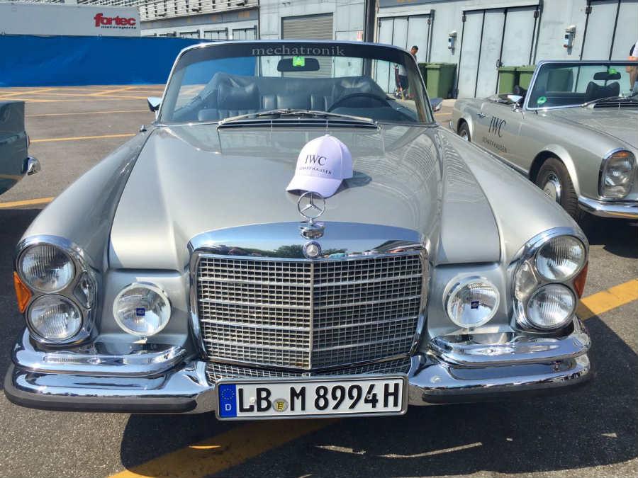 Passione Caracciola: immagine di uno storico Mercedes e sul cofano cappello con logo brand IWC