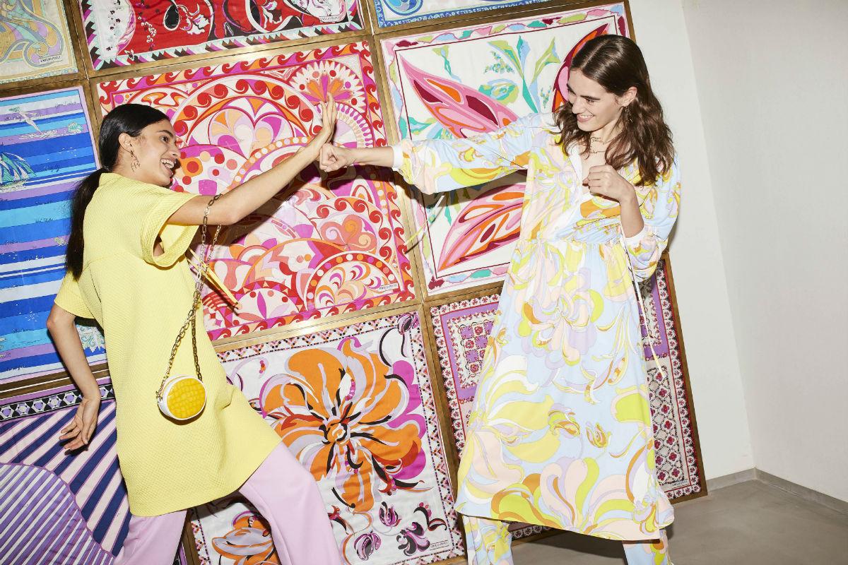 Pre-Collezioni 2018: due modelle. una indossa abito giallo su pantaloni rosa, l'altra indossa abito floreale su pantaloni con la stessa stampa. Entrambe vestono Emilio Pucci