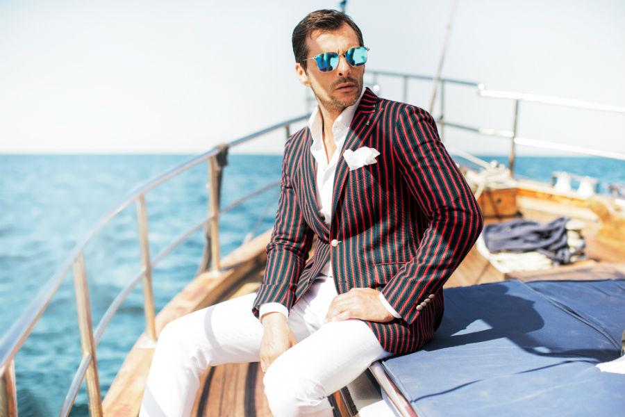 Sartoria Latorre- collezione ss2017-uomo in barca a vela indossa completo giacca fantasia a righe con pochette e pantaloni bianchi