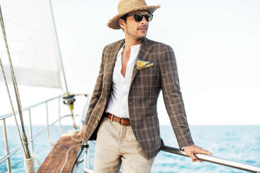 Sartoria Latorre- collezione ss2017-uomoin barca a vela indossa completo giacca fantasia a quadri con pochette e pantaloni beige