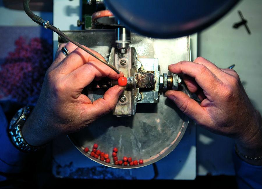 Enzo Liverino - Un'altra fase delicata è quella della bucatura del corallo: il foro deve essere più centrale possibile. In passato la bucatura veniva effettuata senza strumenti automatici, mediante uno speciale archetto a cui era fissato un filo in tensione. La cordicella, annodata attorno a un punteruolo con un ago finale, veniva fatta scorrere avanti e indietro con l'archetto, producendo il moto rotatorio dell'ago, che appoggiato sul corallo, lo forava. In questo tipo di lavorazione, veniva fatta scorrere continuamente dell'acqua sul corallo, per abbassare la temperatura originata dallo sfregamento. Foto Emanuele Zamponi