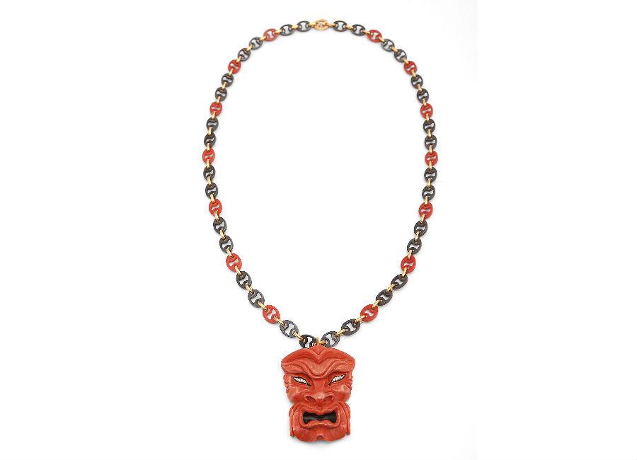 """Enzo Liverino - """"Mascherone"""" (1970), maschera in corallo con fondo in oro, occhi in diamante, catena in corallo e acciaio brunito."""