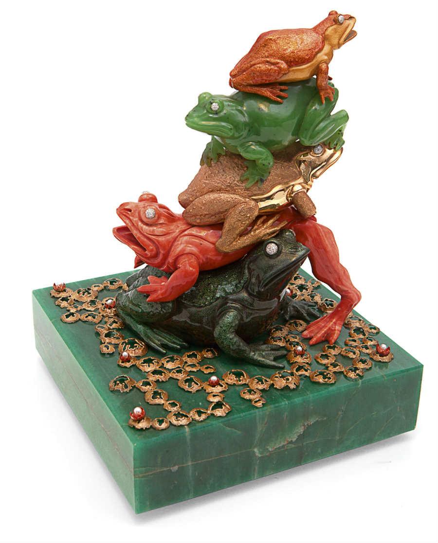 """Enzo Liverino - """"La Babele in palude"""", 1974, è un'opera di virtuosismo tecnico e artistico di proprietà della famiglia Liverino, custodita nel Museo. La base, di avventurina, sostiene una rana in argento smaltato sormontata dalle sue compagne in corallo, oro lucido, giada di Russia e oro smaltato. Le piante di ninfea sono in argento, mentre i fiori sono in oro con perla al centro."""
