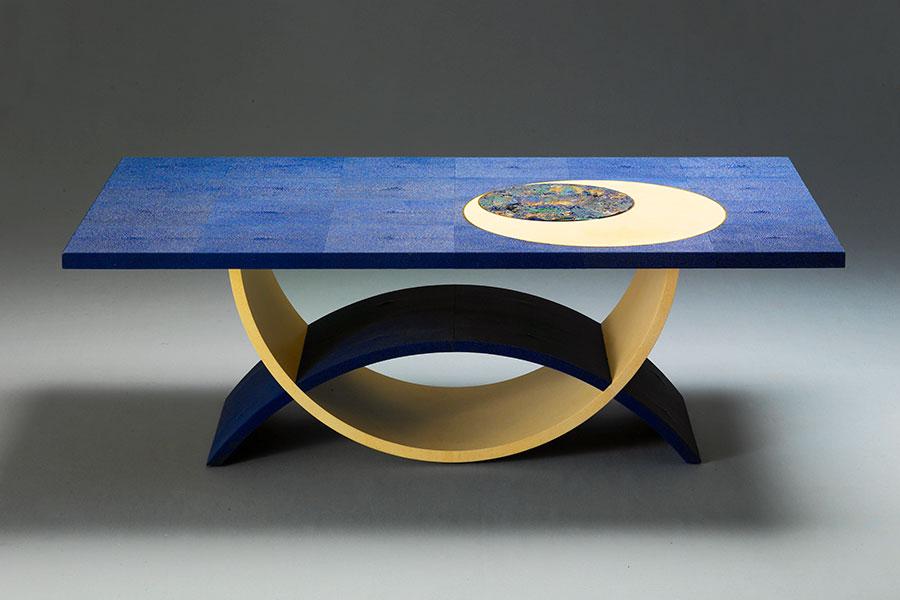 """Giordano Viganò - ebanista - Tavolino """"Blue Moon"""": un tondo in pietra azzurrite (diametro 31,5 cm), caratterizzata da multiformi cromie naturali, risalta accanto a un tondo in pergamena, entrambi contornati da anelli in bronzo. Fanno parte della preziosa decorazione di un piano interamente rivestito in galuchat blu, che compone un tavolo da salotto. La base è formata da due fasce a semicerchio rivestite in galuchat blu e pergamena. Credits: Giordano Viganò"""