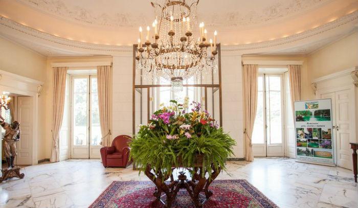 Villa dei Cedri: immagine della lobby decorata con grande lampadario in cristallo, pavimento in marmo e fiori