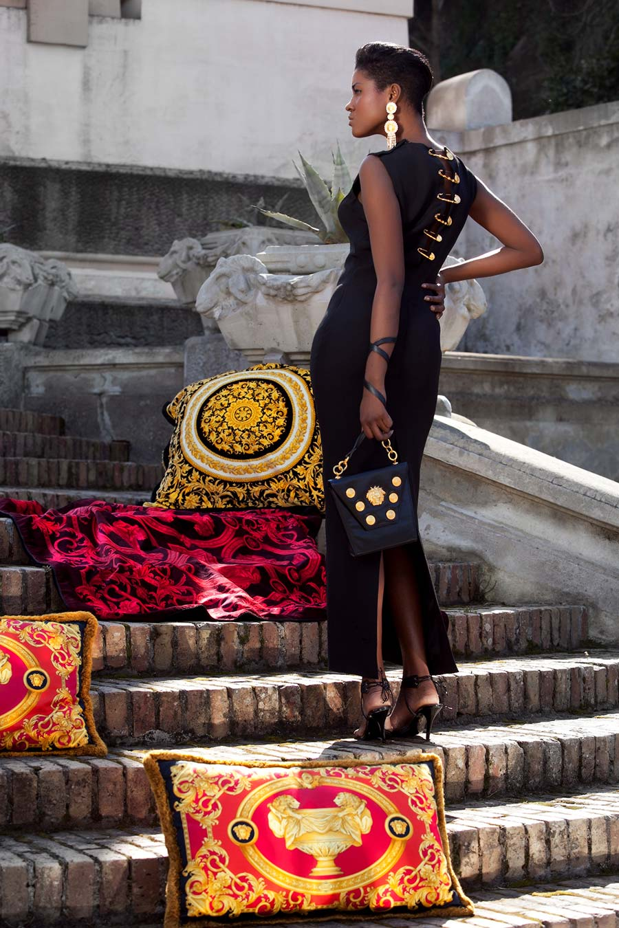 Modella di colore in piedi su di una scalinata di pietra, tra cuscini con logo Versace - Dialoghi / Dissing - Gianni Versace Magna Grecia Tribute (photo©iTrancheseFotografi)