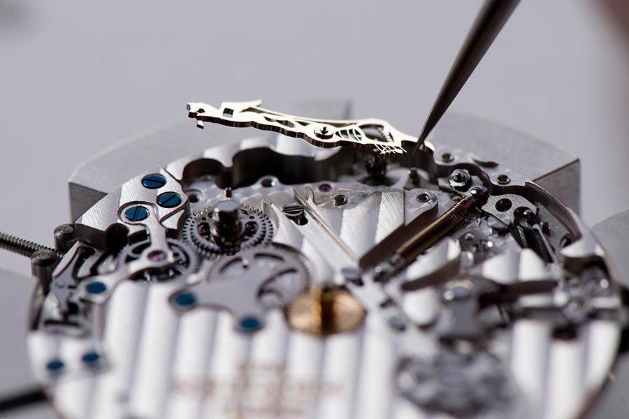 Hermès l'Heure Impatiente - Licenza creativa. Il componente che fa da collegamento tra la ruota che aziona il sub-contatore alle 5 e quella che comanda la lancetta del countdown de l'Heure Impatiente ha la forma di un piccolo cavallino alato.