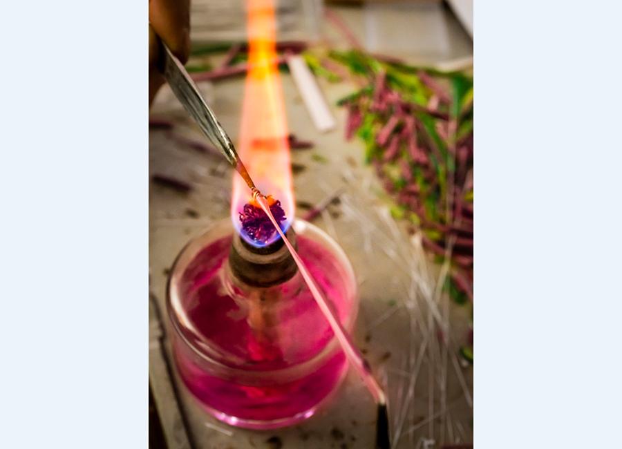 Micro-Mosaico: Nella foto è colta la fase della lavorazione del vetro che viene riscaldato al fuoco di un piccolo lumino per ottenere delle lunghe tessere sottili.