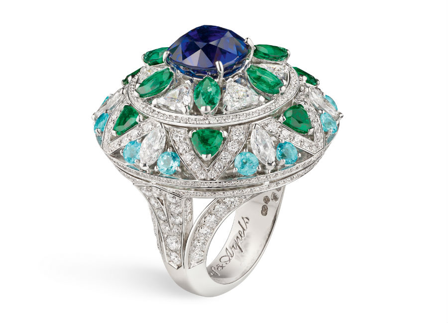Van Cleef & Arpels - Collezione alta gioielleria Le Secret - Anello Fleur Bleue - Oro bianco, diamanti, smeraldi, tormaline Paraíba, uno zaffiro cuscino di 5,13 carati (Birmania). Ad una prima occhiata l'anello ci colpisce per l'importante zaffiro blu, con un tocco discreto ed una rotazione di un quarto di giro, scopriamo poi che il gioiello svela il tratto poetico di Oscar Wilde che cita l'amore paragonandolo alla natura.