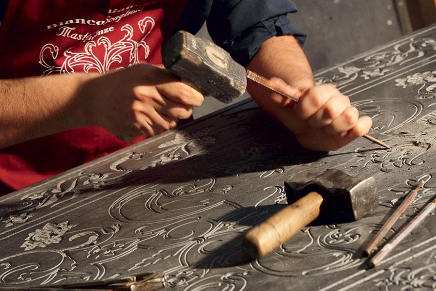 Alessandro Bianchi traccia manualmente, con pazienza, la superficie in marmo da decorare a scagliola aiutandosi solo con mazzuolo e scalpello. Il disegno viene inciso in profondità prima di essere riempito con la miscela di polvere di selenite, pigmenti colorati e colle naturali. © Bianco Bianchi