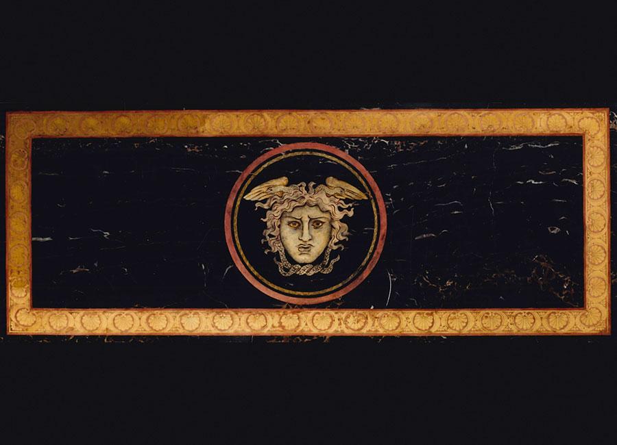 """Piano per consolle intarsiato in scagliola """"Medusa"""" realizzato per Gianni Versace negli anni Ottanta. Al centro del decoro si può notare la testa della gorgone Medusa; si dice che questo tavolo abbia ispirato il suo proprietario nella scelta del logo della Maison Versace. © Bianco Bianchi"""