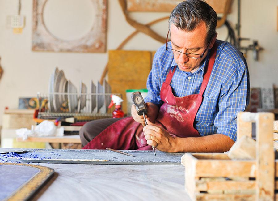 Alessandro Bianchi al lavoro su una superficie da scavare. Questa operazione, come tutte le successive, che conducono al lavoro ultimato, viene realizzata interamente all'interno del laboratorio. © Dario Garofalo, Italia su Misura