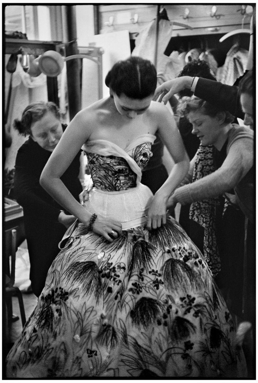 Henri Cartier-Bresson, le mannequin Alla revêt la robe May dans la cabine lors de la Première, 1953 © henri Cartier-Bresson / Magnum Photos
