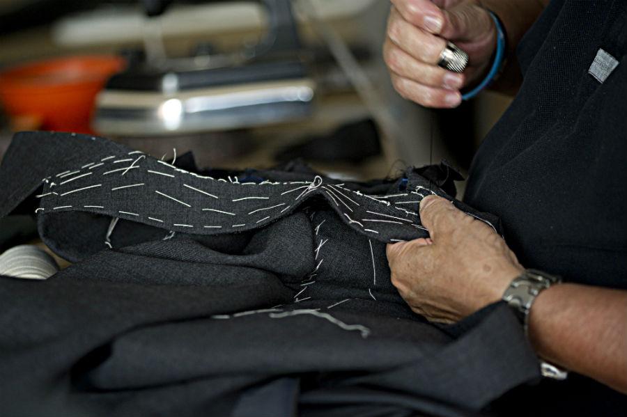 Sartoria Ferdinando Caraceni - la fase dell'imbastitura - un sarto al lavoro su di un abito maschile