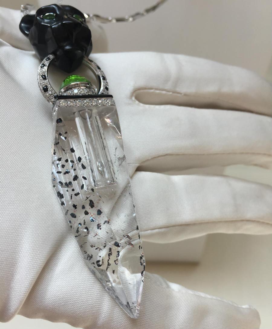 Résonances De Cartier - Ocella – Pendente e collana - flaconcino di cristallo di rocca incluso di mica, tappo di tormalina verde. Testa di pantera scolpita in legno pietrificato nero. Oro bianco, onice, brillanti (7,65 cts). ©TheDucker