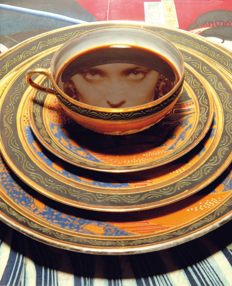 Giovanni Gastel - Scatti per un libro: immagine di una tazzina piena di caffè nella quale si vede riflesso il volto di una donna