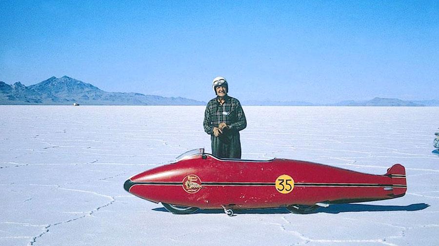 Il neozelandese Burt Munro a Bonneville in una foto del 1976. Con lui la sua Indian Scout del 1920, completamente modificata nel suo capanno lungo un arco di 40 anni per raggiungere la velocità record di 296,11 km/h.