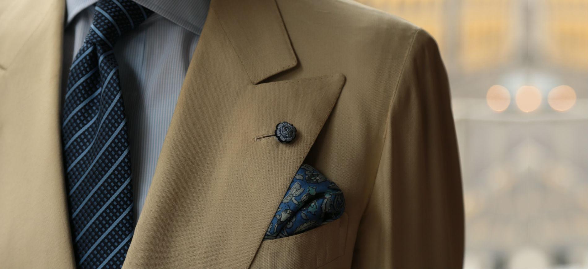 Sartoria A. Caraceni e Carlo Andreacchio: primo piano dettagli giacca con taschino e pochette, indossata su camica bianca con cravatta