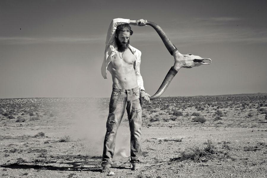 Yuri Catania - fotografo: nell'immagine modello in piedi nel deserto sorregge un teschio di bufalo