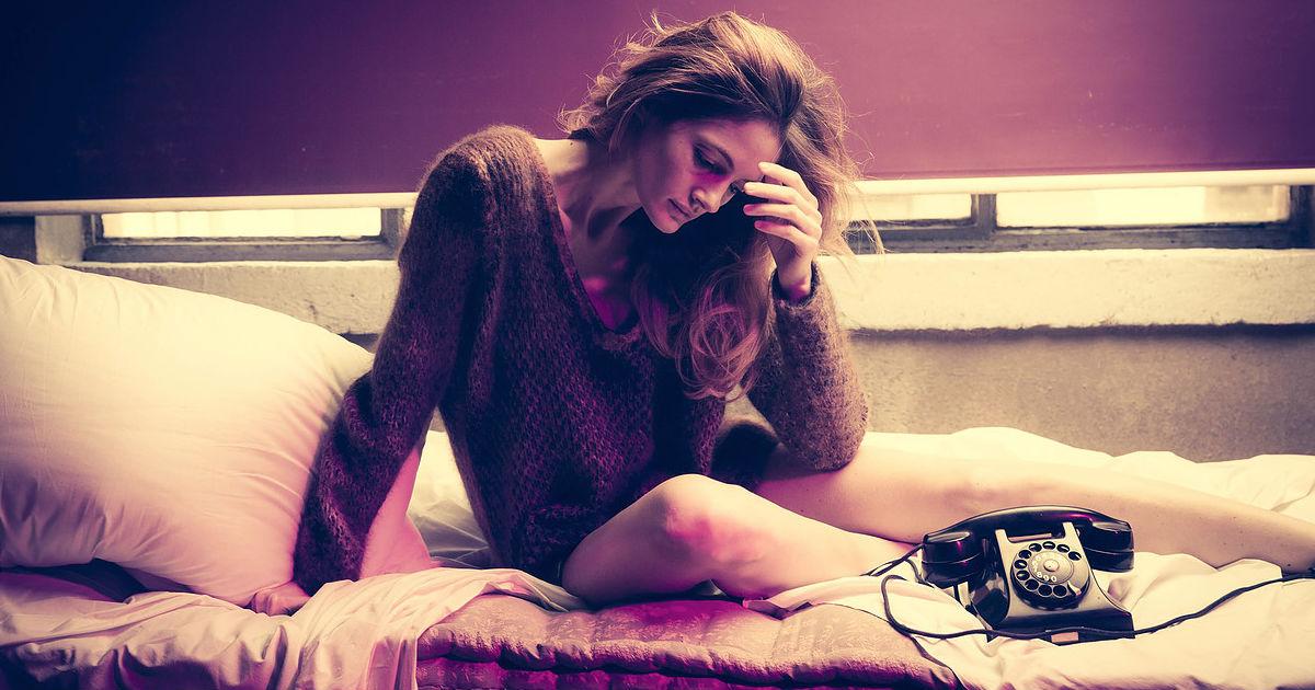 Yuri Catania - fotografo: ragazza in camicia scozzese seduta su di un letto con a finaco un telefono vintage