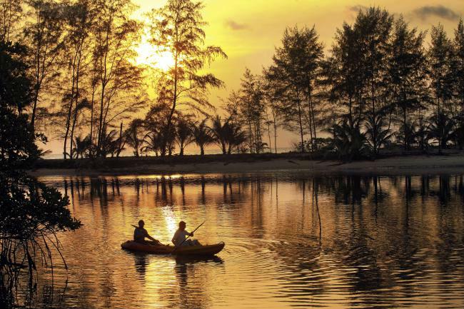 Soneva Kiri - luxury resort in Thailandia: la foresta al tramonto si riflette sull'acqua