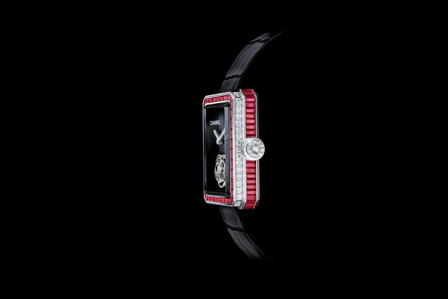 """Manifattura orologiera Chanel - G&F Châtelain, La Chaux-De-Fonds, Svizzera: Un esempio di """"Sertissage Baguette"""" dei rubini su corona e lunetta del segnatempo Première Tourbillon Volante Rubini..Cassa in oro bianco (28.5 x 37mm) con 47 rubini taglio baguette. Quadrante in ceramica nera, tourbillon in oro bianco con 19 diamanti taglio brillante e lancette con 15 diamanti taglio brillante. Lunetta in oro bianco con 38 rubini taglio baguette, 4 diamanti taglio baguette e 52 diamanti taglio brillante. Corona in oro bianco con 16 diamanti taglio baguette e 11 diamanti taglio brillante. Cinturino in alligatore nero con fibbia in oro bianco con 30 diamanti taglio brillante. Movimento meccanico a carica manuale Funzioni: ore, minuti e tourbillon volante. Edizione limitata a 20 esemplari."""