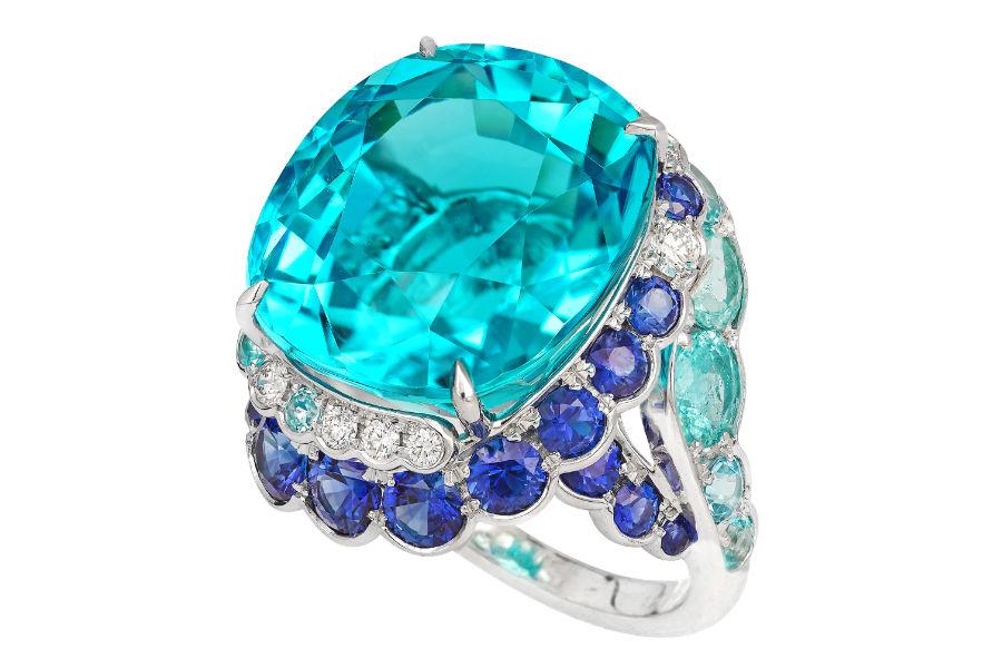 David Morris – Anello Maelstrom in oro bianco, una tormalina Paraiba del Mozambico di 20,13 cts, tormaline paraiba taglio rotondo (totale 2,22 cts), brillanti (0,22 cts), diamanti taglio fantasia (0,05 cts), zaffiri blu taglio rotondo (totale 2,66 cts).