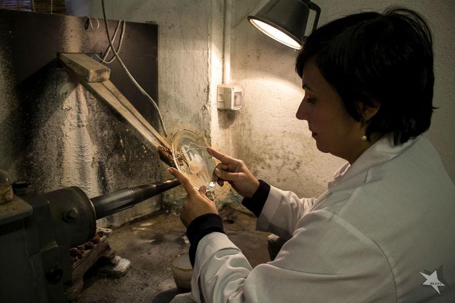 All'interno del suo laboratorio Vanessa Cavallaro al lavoro davanti al tornio mentre incide le forme di un paesaggio su un piattino in vetro, materia che la Maestra artigiana padroneggia con perizia e passione. Immagine © Ida Luce