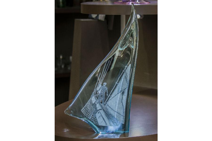 Vela in cristallo blu chiaro, soffiata a bocca (30cm x 50cm). Le incisioni hanno come protagonisti marinai e particolari di una prua. Opera a cura di Vanessa Cavallaro