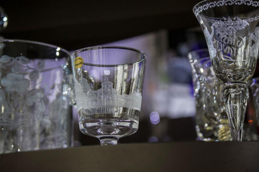 """In primo piano, bicchiere realizzato per la Reggia di Venaria Reale; l'incisione è uno scorcio della stessa Reggia. A fianco sulla destra, un calice in cristallo con gambo soffiato che rappresenta l'incisione di una rosa con due putti e la dicitura """"The Guild of Glass Engravers"""", associazione londinese di cui Vanessa Cavallaro fa parte."""